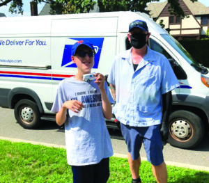 Matthew with a miniature postal service truck and Phil the letter carrier.