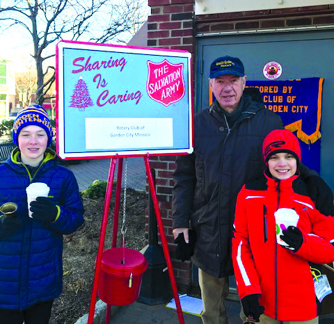 Past Rotary District Governor and Past Club President Thomas Gelsdorf assisted by two Garden City Boy Scouts at a previous Red Kettle Bell Ring.
