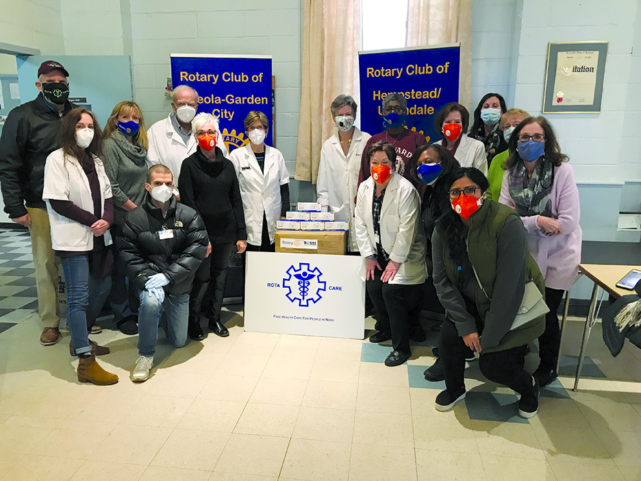 group of people wearing masks posing with RotaCare banner