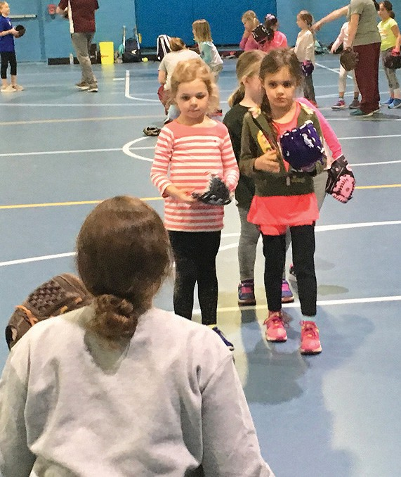 Kindergarten and first-grade players work with HS Varsity players.