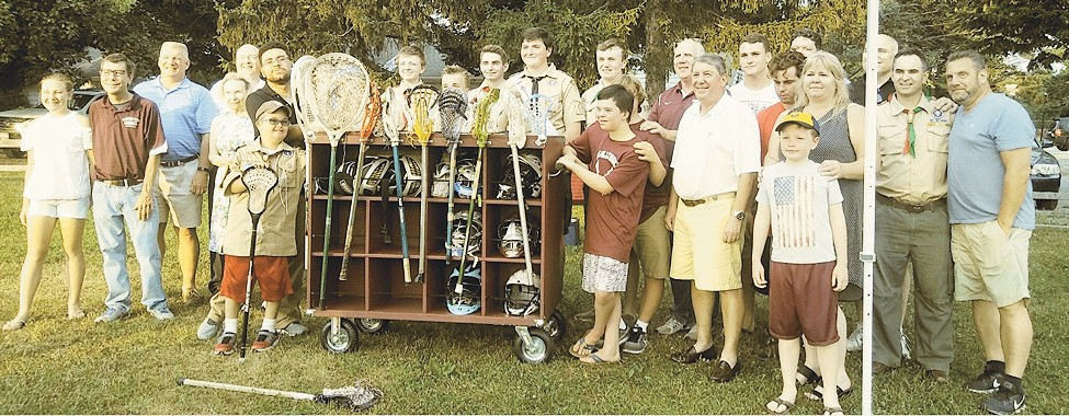 Members of the Garden City Lacrosse team, Boy Scout Troop #134 , Mark Hyer (Garden City Trustee), John Delany (Garden City Trustee) and Theresa Trouvé (Garden City Deputy Mayor) presenting the all terrain equipment cart designed and built by Jack Ryan.